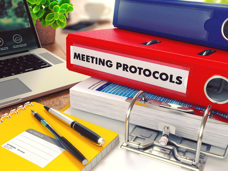 timelines: Meeting Protocols - Red Office Folder on Background of Working Table with Stationery, Laptop and Reports. Business Concept on Blurred Background. Toned Image.