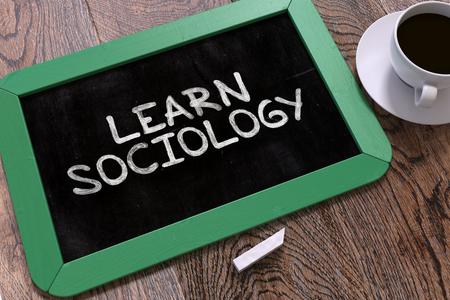 sociology: Cita de motivación manuscrita - Aprenda Sociología - en una pizarra verde. Vista superior Composición con la pizarra y blanco taza de café.