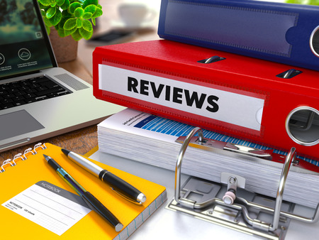 revision: Red Ring Binder with Inscription Reviews on Background of Working Table with Office Supplies, Laptop, Reports. Toned Illustration. Business Concept on Blurred Background.