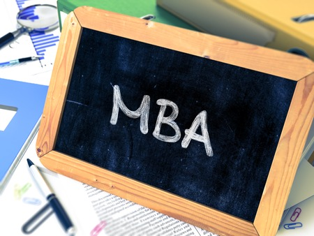 master degree: MBA - Master Business Administration - Concept Hand Drawn on Chalkboard on Working Table Background. Blurred Background. Toned Image.