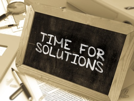 presently: Time for Solutions Handwritten on Chalkboard. Composition with Small Chalkboard on Background of Working Table with Ring Binders, Office Supplies, Reports. Blurred Background. Toned Image.