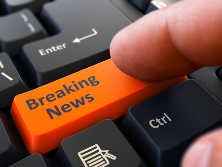 urgent announcement: Breaking News Orange Button - Finger Pushing Button of Black Computer Keyboard. Blurred Background. Closeup View.