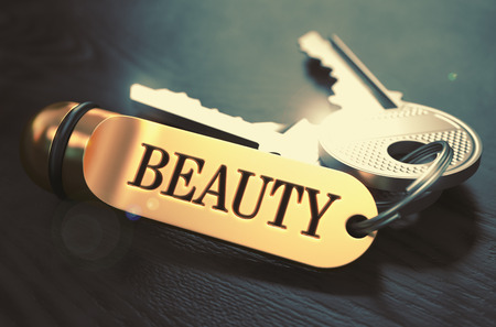 enchantment: Beauty - Bunch of Keys with Text on Golden Keychain. Black Wooden Background. Closeup View with Selective Focus. 3D Illustration. Toned Image.