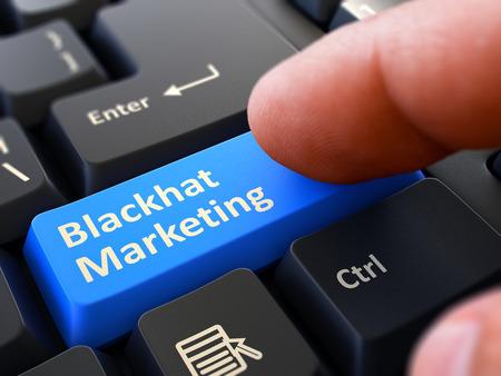 cpl: Blackhat Marketing - Written on Blue Keyboard Key. Male Hand Presses Button on Black PC Keyboard. Closeup View. Blurred Background.