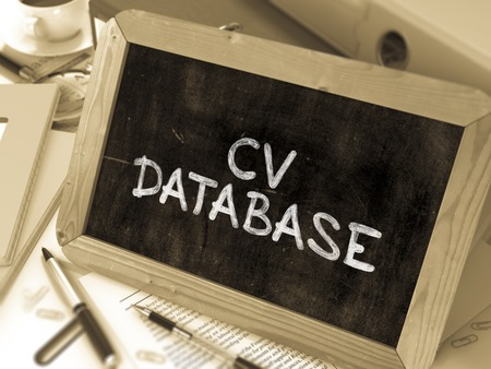 hoja de vida: CV Base de datos Concepto Mano dibujada en la pizarra en la Mesa de Trabajo de fondo. Fondo enmascarado. Imagen virada. Foto de archivo