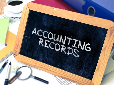 registros contables: Accounting Records - Chalkboard with Hand Drawn Text, Stack of Office Folders, Stationery, Reports on Blurred Background. Toned Image.