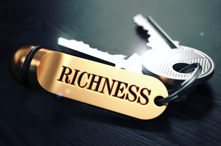 opulence: Keys and Golden Keyring with the Word Richness over Black Wooden Table with Blur Effect. Toned Image. Stock Photo