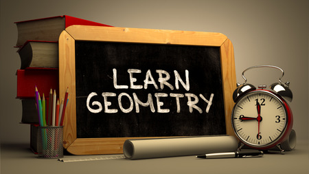 Learn Geometry - Chalkboard with Hand Drawn Inspirational Quote, Stack of Books, Alarm Clock and Rolls of Paper on Blurred Background. Toned Image.
