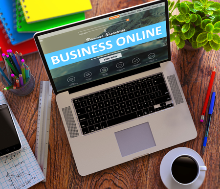 web portal: Business Online Concept. Modern Laptop and Different Office Supply on Wooden Desktop background.