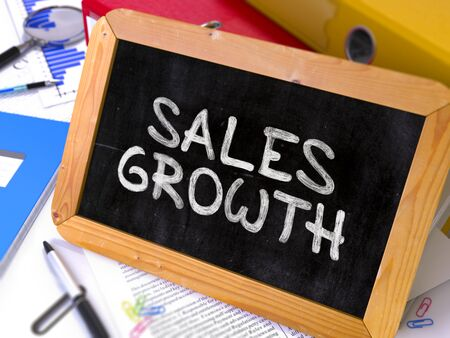 sales growth: Handwritten Sales Growth on a Chalkboard. Composition with Chalkboard and Ring Binders, Office Supplies, Reports on Blurred Background. Toned Image. Stock Photo