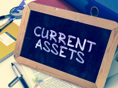 cash flow statement: Current Assets - Chalkboard with Hand Drawn Text, Stack of Office Folders, Stationery, Reports on Blurred Background. Toned Image.