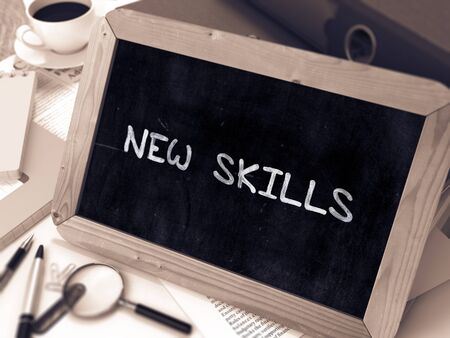learning new skills: New Skills - Chalkboard with Hand Drawn Text, Stack of Office Folders, Stationery, Reports on Blurred Background. Toned Image. Stock Photo