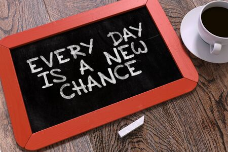 every: Hand Drawn Motivation Quote - Every Day is a New Chance - on Small Red Chalkboard. Business Background. Top View.