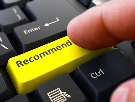 El dedo presiona botón amarillo de recomendaciones sobre antecedentes de teclado Negro. Primer punto de vista. Enfoque selectivo. Foto de archivo