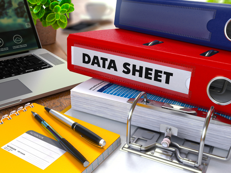 data sheet: Red Ring Binder with Inscription Data Sheet on Background of Working Table with Office Supplies, Laptop, Reports. Toned Illustration. Business Concept on Blurred Background.