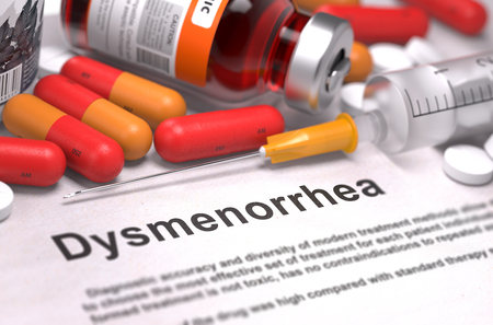 ovaries: Dysmenorrhea - Printed Diagnosis with Blurred Text. On Background of Medicaments Composition - Red Pills, Injections and Syringe. Stock Photo