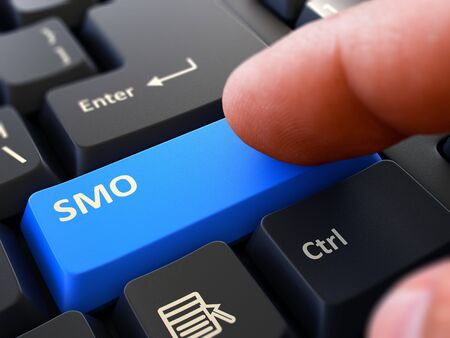 smo: SMO - Social Media Optimization - Written on Blue Keyboard Key. Male Hand Presses Button on Black PC Keyboard. Closeup View. Blurred Background. Stock Photo