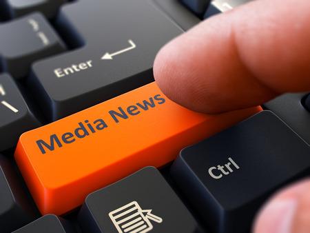 keyboard: Finger Presses Orange Button  Media News on Black Keyboard Background. Closeup View. Selective Focus. Stock Photo