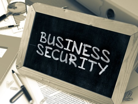trade secret: Business Security Handwritten by White Chalk on a Blackboard. Composition with Small Chalkboard on Background of Working Table with Office Folders, Stationery, Reports. Blurred, Toned Image. Stock Photo