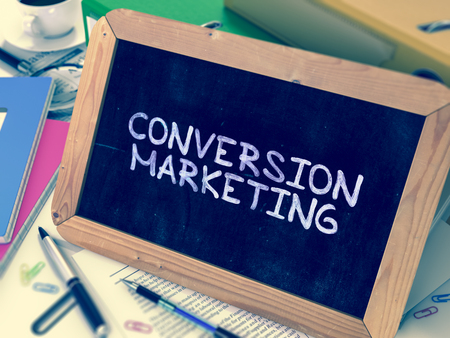 insights: Conversion Marketing Handwritten by White Chalk on a Blackboard. Composition with Small Chalkboard on Background of Working Table with Office Folders, Stationery, Reports. Blurred, Toned Image. Stock Photo