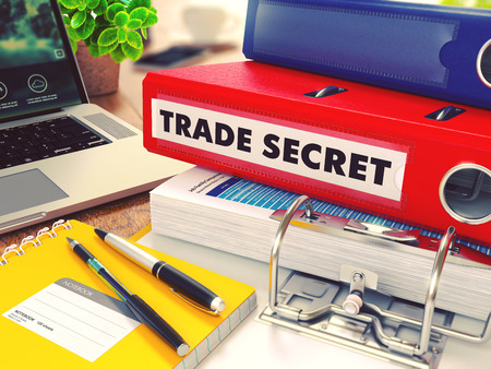 trade secret: Trade Secret - Red Office Folder on Background of Working Table with Stationery, Laptop and Reports. Business Concept on Blurred Background. Toned Image. Stock Photo