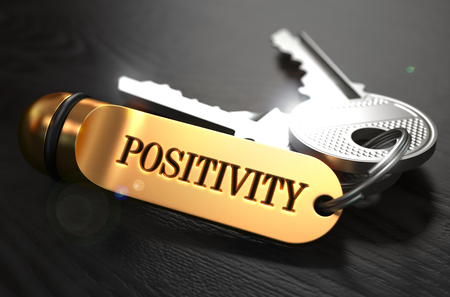 keyring: Positivity  Concept. Keys with Golden Keyring on Black Wooden Table. Closeup View, Selective Focus, 3D Render.