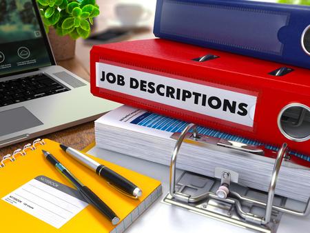 Red Ring Binder met inscriptie Job beschrijvingen op de achtergrond van de werktafel met Office Supplies, Laptop, Reports. Afgezwakt Illustratie. Business Concept op onscherpe achtergrond. Stockfoto