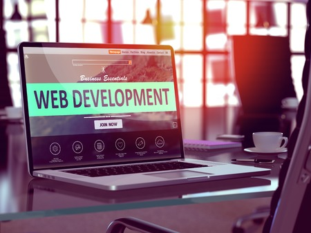 Web Development Concept. Closeup Landing Page on Laptop Screen  on background of Comfortable Working Place in Modern Office. Blurred, Toned Image. Banco de Imagens