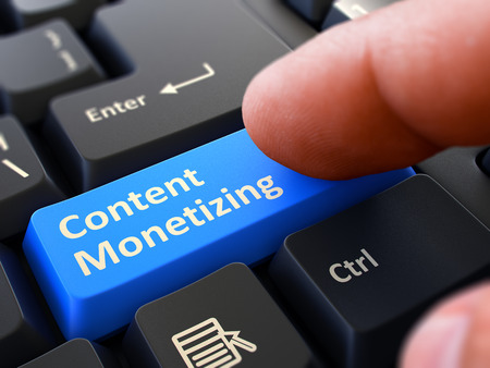 monetize: Content Monetizing Button. Male Finger Clicks on Blue Button on Black Keyboard. Closeup View. Blurred Background.