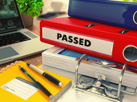 passed test: Red Office Folder with Inscription Passed on Office Desktop with Office Supplies and Modern Laptop. Business Concept on Blurred Background. Toned Image. Stock Photo