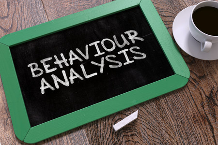 responsibility survey: Behaviour Analysis - Green Chalkboard with Hand Drawn Text and White Cup of Coffee on Wooden Table. Top View.