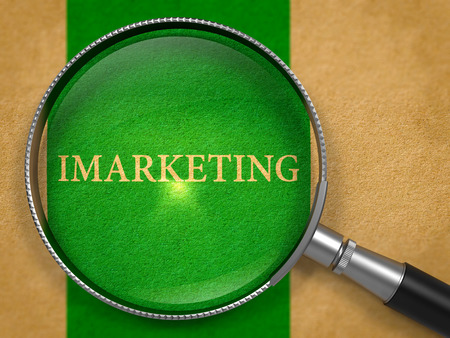 monetizing: IMarketing through Loupe on Old Paper with Green Vertical Line Background. Stock Photo