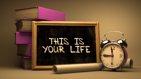 this: This is Your Life Handwritten by white Chalk on a Blackboard. Composition with Small Chalkboard and Stack of Books, Alarm Clock and Rolls of Paper on Blurred Background. Toned 3d Illustration.