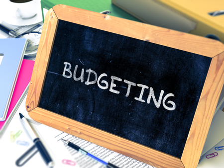 Budgeting Concept Hand Drawn on Chalkboard on Working Table Background. Blurred Background. Toned Image. 3d Illustration.