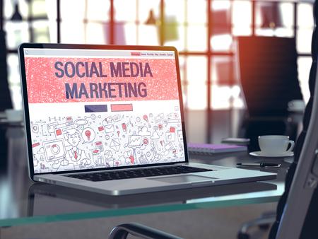 interaccion social: Lugar de trabajo moderno con la computadora portátil que muestra la página de destino en el estilo del diseño del Doodle con el texto Social Media Marketing. Imagen virada con enfoque selectivo.