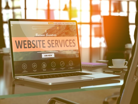 Website Services Concept. Closeup Landing Page on Laptop Screen on background of Comfortable Working Place in Modern Office. Blurred, Toned Image.