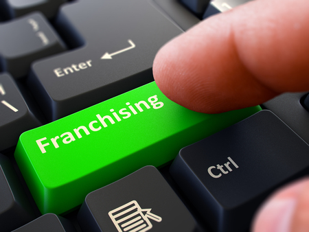 franchising: Franchising Button. Male Finger Clicks on Green Button on Black Keyboard. Closeup View. Blurred Background.