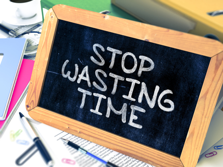 wasting: Stop Wasting Time - Chalkboard with Hand Drawn Text, Stack of Office Folders, Stationery, Reports on Blurred Background. Toned Image.
