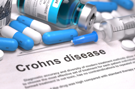 gastroenterologist: Crohns Disease - Printed Diagnosis with Blurred Text. On Background of Medicaments Composition - Blue Pills, Injections and Syringe. 3d Render.