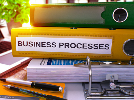 structuring: Business Processes - Yellow Office Folder on Background of Working Table with Stationery and Laptop. Business Processes Business Concept on Blurred Background. Business Processes Toned Image. 3D