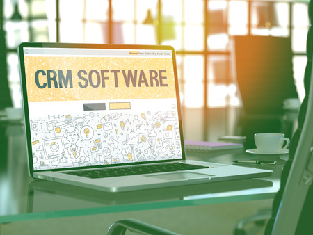 CRM - Customer Relationship Management - Software - Closeup Landing Page in Doodle Design Style on Laptop Screen. On Background of Comfortable Working Place in Modern Office. Toned, Blurred Image.