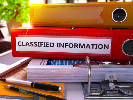 undisclosed: Red Office Folder with Inscription Classified Information on Office Desktop with Office Supplies and Modern Laptop. Classified Information Business Concept on Blurred Background. 3D Render Stock Photo