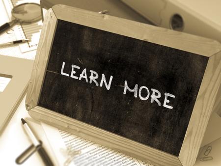 Meer informatie Handgeschreven op schoolbord. Samenstelling met kleine schoolbord op achtergrond van de werktafel met ringbanden, kantoorbenodigdheden, rapporten. Onscherpe achtergrond. Getinte afbeelding. 3D render. Stockfoto