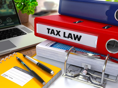tax law: Red Ring Binder with Inscription Tax Law on Background of Working Table with Office Supplies, Laptop, Reports. Toned Illustration. Business Concept on Blurred Background. 3d Render.