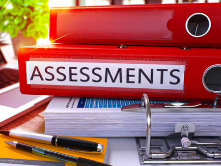 assessments: Red Office Folder with Inscription Assessments on Office Desktop with Office Supplies and Modern Laptop. Assessments Business Concept on Blurred Background. Assessments - Toned Image. 3D
