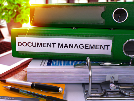 Green Office Folder with Inscription Document Management on Office Desktop with Office Supplies and Modern Laptop. Document Management Business Concept on Blurred Background. 3D Render. Stock Photo