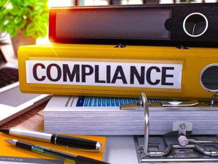 Gelb Ringbuch mit Beschriftung Konformität auf Hintergrund der Arbeitstisch mit Büromaterial und Laptop. Compliance-Business-Konzept auf unscharfen Hintergrund. 3D übertragen. Lizenzfreie Bilder - 52232524