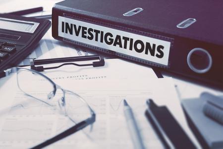 Carpeta de anillas con las investigaciones de inscripción en el fondo de la mesa de trabajo con material de oficina, vasos, Informes. Ilustración tonificado. Concepto de negocio en el fondo borroso.