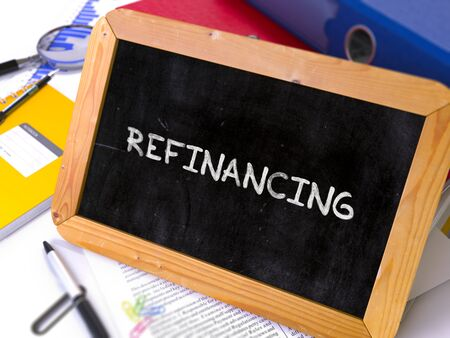 refinancing: Handwritten Refinancing on a Chalkboard. Composition with Chalkboard and Ring Binders, Office Supplies, Reports on Blurred Background. Toned Image. 3D Render.