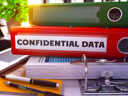 Confidential Data - Red Office Folder on Background of Working Table with Stationery and Laptop. Confidential Data Business Concept on Blurred Background. Confidential Data Toned Image. 3D.